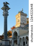 Loggia of Saint James, Saint Mark winged lion column and clock tower at sunset in Libertà square in Udine, Italy
