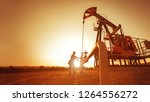 Small photo of Oil worker is checking the pump near oil derrick on the sunset background.