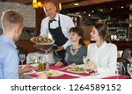 handsome waiter serving pizza... | Shutterstock . vector #1264589152