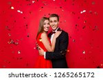Portrait of two nice sweet tender lovely attractive gorgeous elegant chic cheery positive people hugging among flying decorative elements new year xmas isolated over bright vivid shine red background