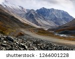 Epic landscape with a road on a mountain pass. Around majestic rocky mountains with snow-capped peaks. In the gorge a small river. Iultin highway, Iskaten Ridge, Chukotka, Far East of Russia. Arctic.