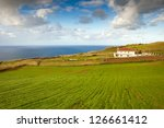 Farm house at the ocean coast under heavy clouds, Azores, Portugal - stock photo