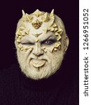 Small photo of Man with dragon skin and beard. Monster with frowning face and white eyes. Alien or reptilian makeup with sharp thorns and warts. Demon head on black background. Horror and fantasy concept.