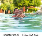 father and child swimming in... | Shutterstock . vector #1267665562
