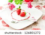 Fresh strawberries  as romantic dessert  on a plate in heart shape of berry sauce. selective focus - stock photo
