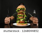 man with cutlery eating huge... | Shutterstock . vector #1268044852