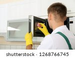 male janitor cleaning microwave ... | Shutterstock . vector #1268766745