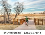 mature male cyclist on a newly constructed bike trail in a typical winter scenery without snow in Fort Collins in northern Colorado