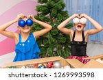 two girls put big christmas... | Shutterstock . vector #1269993598