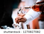Stock photo pour white red wine and rose from the decanter and glass into the glass 1270827082
