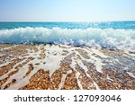 Splash Of Sea Foam On A Sandy...