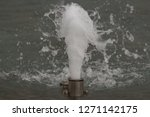 Small photo of water spout water plume in fountain in park close up of water spurt white bubbles steel spout in city