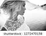 woman in a big white hat stands ...   Shutterstock . vector #1272470158