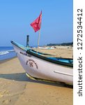 Small photo of Goa, India - Novamber 05, 2018: white fisherman boat with red flag on the sand beach in Mandrem village, North Goa. India is one of the birthplace of swastika, which fishermen often draw on their boat