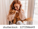 Stock photo attractive girl embracing her pet with smile indoor portrait of cute ginger woman playing with cat 1272586645