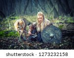 Small photo of Outdoor northern warrior woman with braided hair and war makeup holding shield and ax with wolf next to her ready to attack - Movie theme of woman warrior viking in forest - Cinematic and movie filter