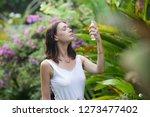 woman spraying facial mist on...   Shutterstock . vector #1273477402