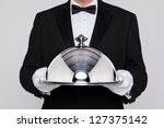 Stock photo waiter serving a meal under a silver cloche or dome 127375142