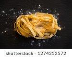 dry tagliatelle pasta on black... | Shutterstock . vector #1274252572