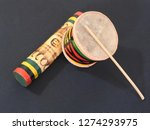 """Small photo of Close-up of two colorful handmade Brazilian percussion instruments: small drum with drumstick and """"ganzá"""", a type of rattle. They are widely used to accompany the samba music. Black background."""