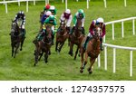 Stock photo race horses and jockeys taking the final turn on the race track 1274357575