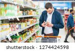 Small photo of At the Supermarket: Handsome Man Uses Smartphone and Looks at Nutritional Value of the Canned Goods. He's Standing with Shopping Cart in Canned Goods Section.