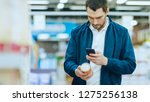 Small photo of At the Supermarket: Handsome Man Uses Smartphone to Check Nutritional Value of the Canned Goods and Buy it. He's Standing with Shopping Cart in Canned Goods Section.