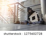 homeless man is sitting down on ... | Shutterstock . vector #1275602728