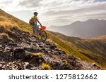 biker pushes his bicycle up in... | Shutterstock . vector #1275812662