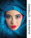 Fine art portrait of woman with colorful makeup in blue turban (looking at camera) - stock photo