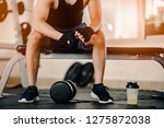 muscular man at gym taking a... | Shutterstock . vector #1275872038