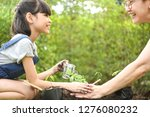 a girl and parent planting... | Shutterstock . vector #1276080232