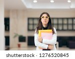 Stock photo confused businesswoman holding paperwork in office building funny nervous employee waiting for job 1276520845