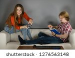 couple sitting on couch... | Shutterstock . vector #1276563148