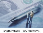 Double exposure row of coins of Two Business man and graph,saving,investment and finance concepts. Miniature people Stand behind of a red pen,soft focus and blurred style.