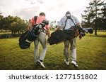 Small photo of Rear view of two senior golf players walking together in the golf course with their golf bags. Senior golfers walking out of the course after the game.
