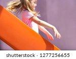 young girl sliding down orange... | Shutterstock . vector #1277256655