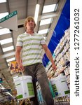 young man buying tins of paint... | Shutterstock . vector #1277261032