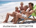 family in deckchairs on sandy... | Shutterstock . vector #1277269708