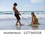 teenage couple playing on beach ... | Shutterstock . vector #1277365528