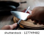 Man Sharpening The Knife To Cu...