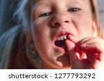 a little girl shows a wobbly... | Shutterstock . vector #1277793292