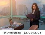 asian woman holding folder of... | Shutterstock . vector #1277892775
