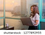 smiling asian woman with laptop ... | Shutterstock . vector #1277892955