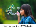 Asian Little Girl Is Blowing A...