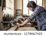 Skilled woodworker wearing safety gear using a mitre saw to cut a piece of wood while working alone in his woodworking studio - stock photo