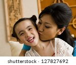 mother giving daughter a kiss... | Shutterstock . vector #127827692