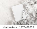 Small photo of Fuzzy white fur plaid and and white notebook on marble table. Flat lay, top view, copy space
