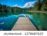 Landscape panorama of Crestasee - Lake Cresta, municipalities of Flims and Trin in the Grisons, Switzerland. Wooden dock on the lake.