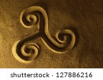 Small photo of Celtic triskele hand drawn in the sand